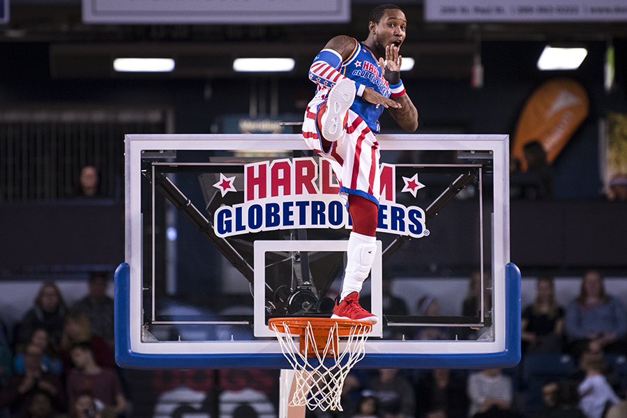 "St. Catharines, ON - April 12: ""Primetime"" Maberry of the Harlem Globetrotters strikes a pose while standing on the rim of a basketball net during their April 12 game in St. Catharines, ON."
