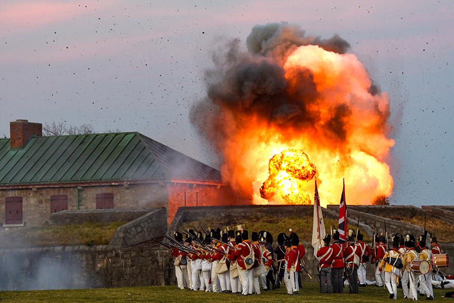 An explosion rises above Old Fort Erie during a battle re-enactment of the Siege of Fort Erie, in Fort Erie, Ont.