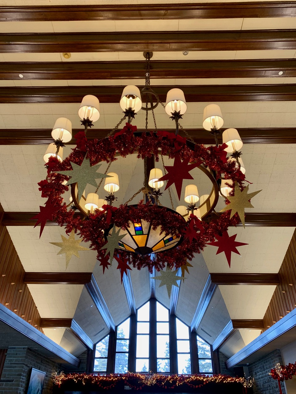 What an entrance! Gorgeous high ceilings, wood beams and a massive chandelier decorated for Christmas in the Jasper Park Lodge main lobby. Photo by: Lighter Side Interiors