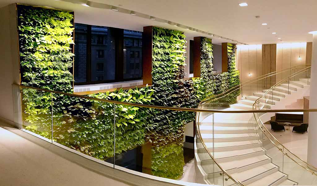 """What are the benefits of biophilic design in the workplace? - Research into the benefits of biophilic design has gone a long way to explaining the various health benefits associated with bringing nature indoors.Environment psychologist Stephen Kaplan says that nature powerfully engages the mind with """"involuntary fascination"""" which helps restore attention and focus. He also says that people can concentrate better after spending time in nature. In addition, people with a view of natural elements, such as trees, water or countryside, report greater levels of wellbeing than those looking over more urban settings, according to the Human Spaces Report.The World Health Organisation expects stress related illness, such as mental health and cardio-vascular disease, to be the biggest contributor to disease by 2020.It has been shown that incorporating elements of nature, either directly or indirectly, into the workplace can reduce stress, blood pressure and heart rate, as well as boost productivity and creativity. In fact, biophilic design in the workplace can increase productivity by 8%, and well-being by 13%, helping to reduce absenteeism."""