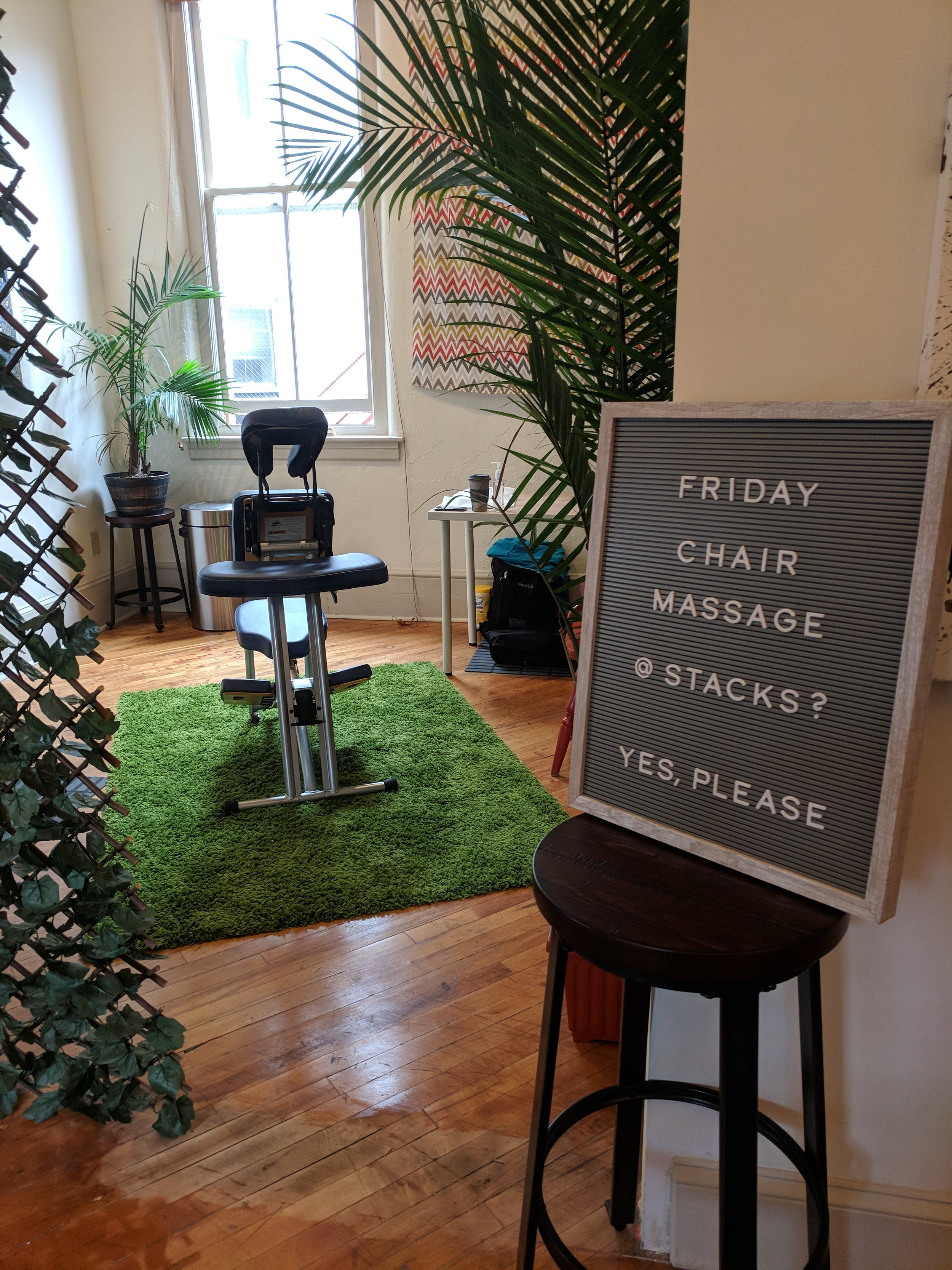 Massage chair in room with sign Friday Chair Massage at Stacks co-working