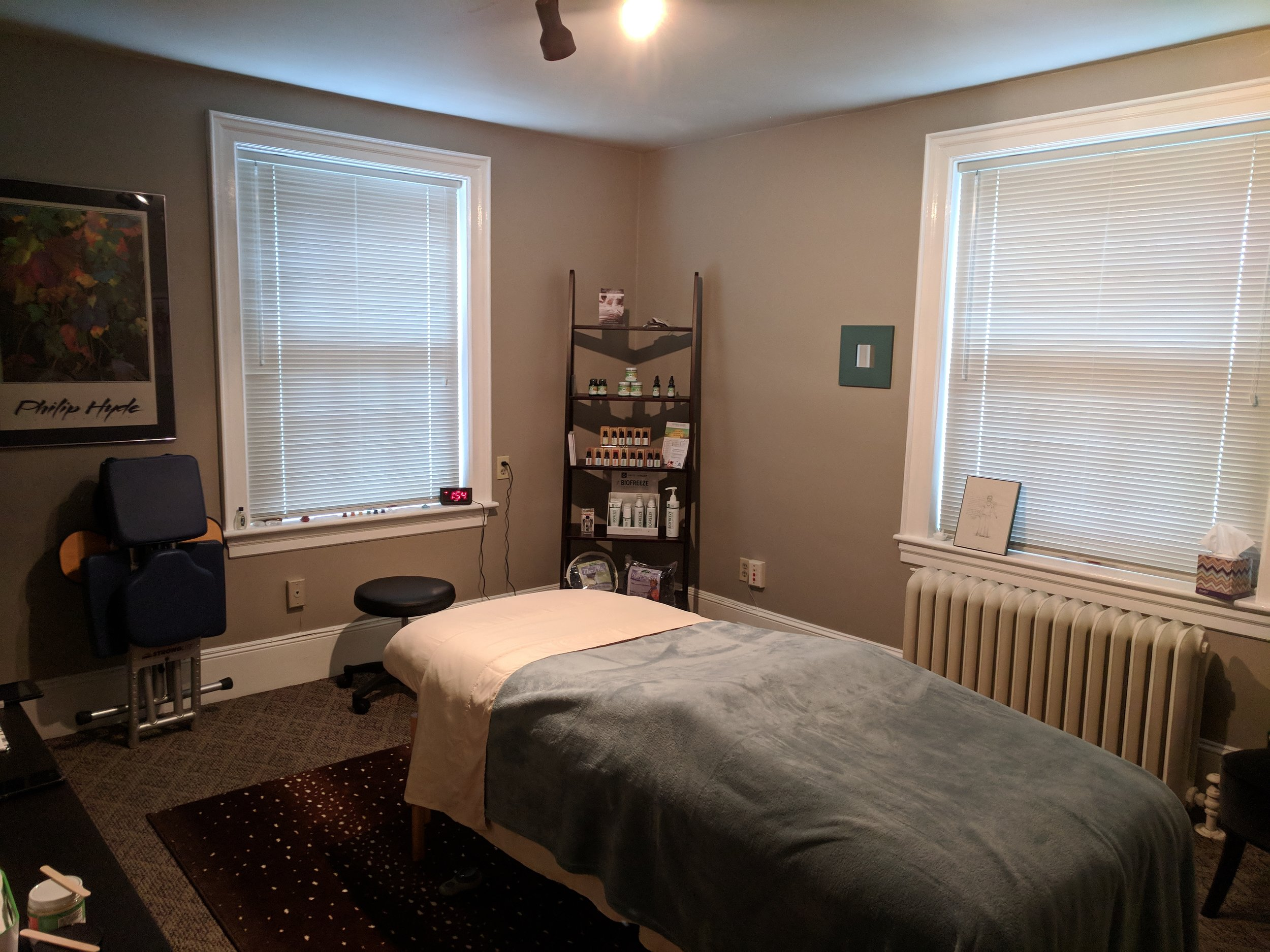 Massage studio with massage table and retail shelf