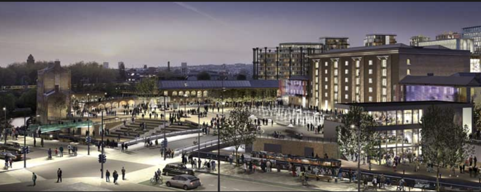 A night time view of Granary Square, part of the Kings Cross development. The circular structure in the background is one of the blocks of flats built inside an old gas tank frame