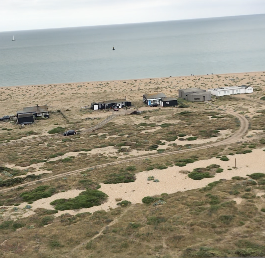 A stretch of the shingle beach at Dungeness, with a small cluster of traditional and modern resident's houses backing on to it