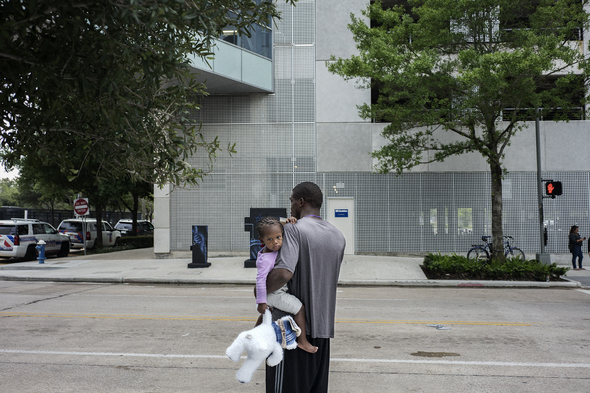 A little girl and her father outside of the Houston Convention Center.