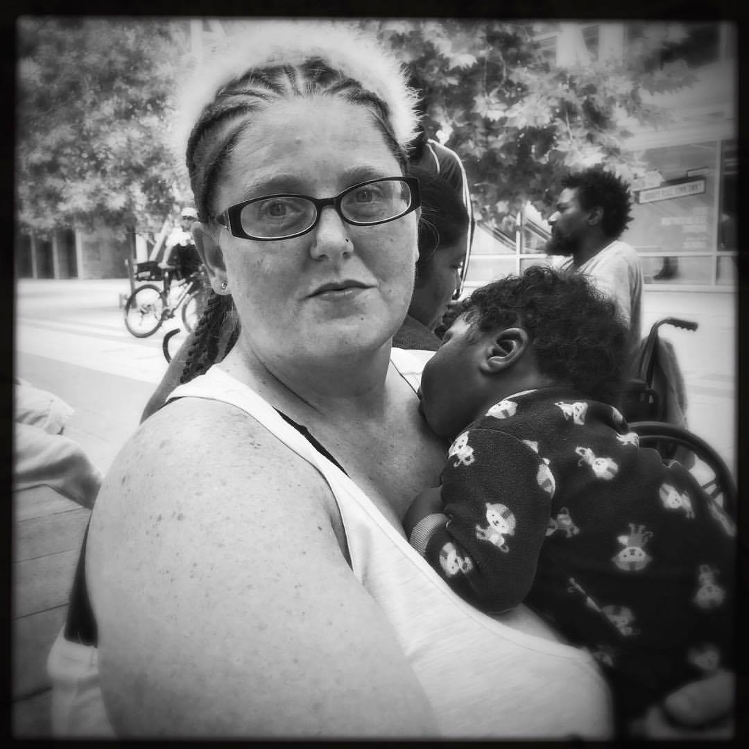 Saptember 1, 2017 This is Amber. She evacuated to the  #houstonconvention  center after water rapidly rose in her home. As she fled the water she was mugged while seeking refuge, losing what little she had. She wasn't bitter about it, but said she had to keep going, thankful to be alive. The little boy she's holding is Joshua, 3 months old today. Joshua is not her child but the boy of a woman whom she made friends with in the shelter. Wanting to give Joshua's mom a rest, Amber took the child into her own arms, in 102f degree(39C) heat. Such generosity is not uncommon to what I've witnessed the past 3 days, but is tremendously special.   #harvey ,  #hurricaneharvey ,  #hurricane ,  #houston ,  #texas , #climatechange ,  #climatechangeisreal ,  #healing