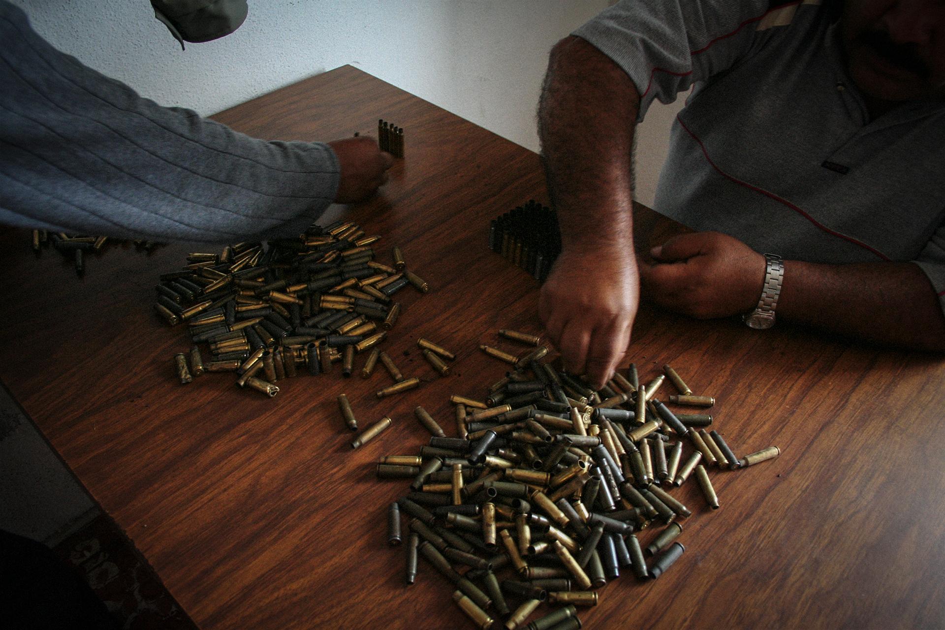 A police official sorts bullets after a drug murder.