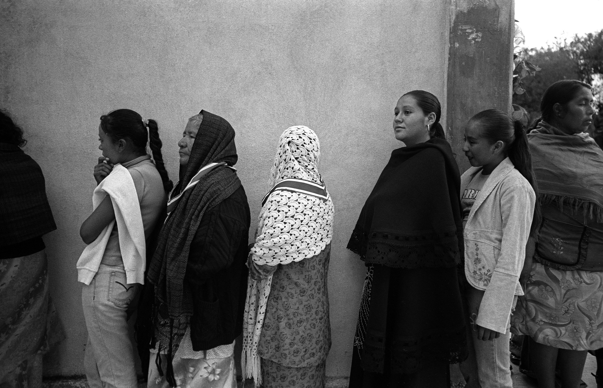 Residents of El Gusano wait in line at the village church to take communion on their saint day.