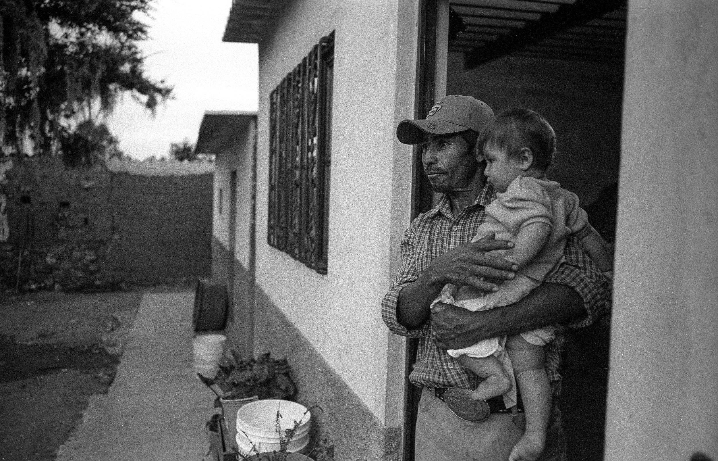 Cipriano Paris holds his youngest son Ricardo, 7 months, after working in his corn field and attending to his cattle.