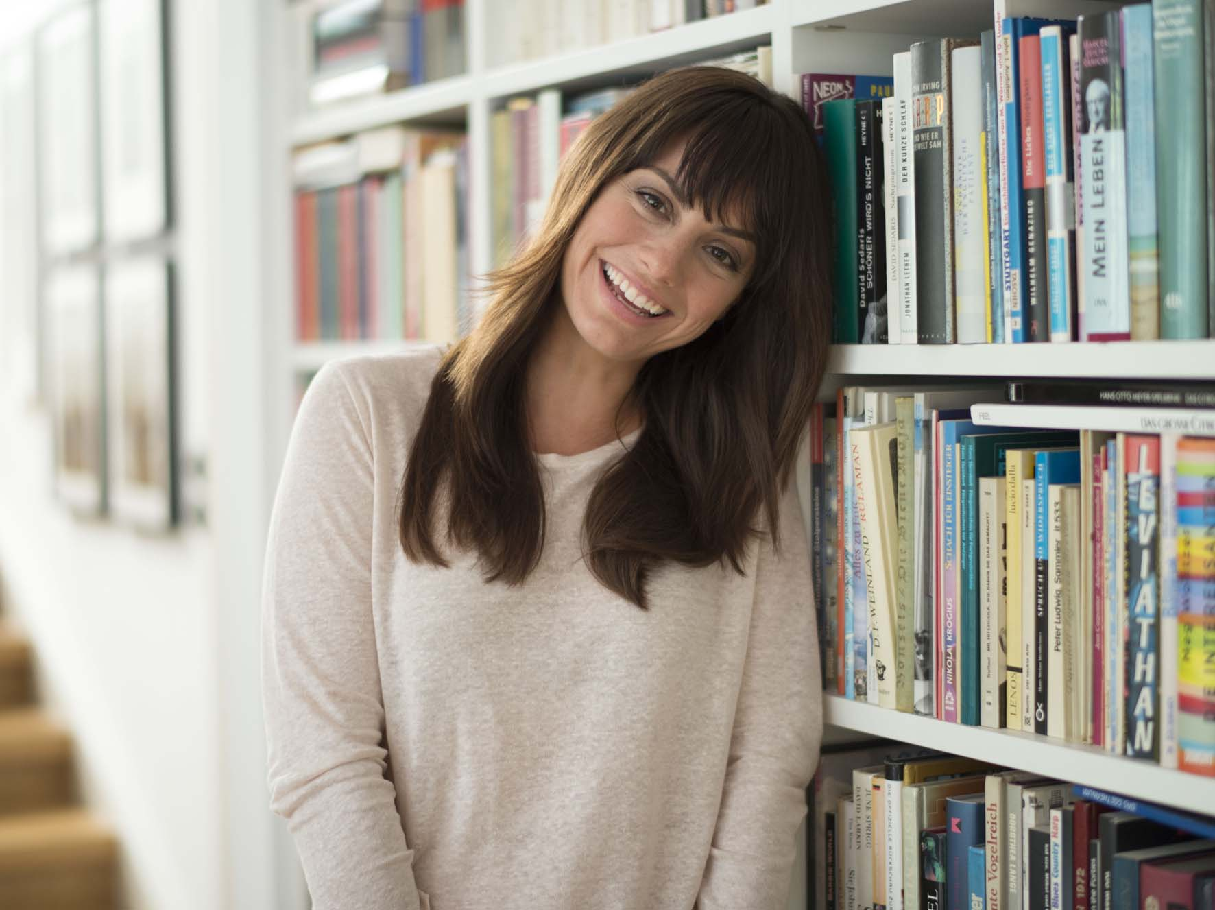Commercial Model Cora lachend in der Bibliothek