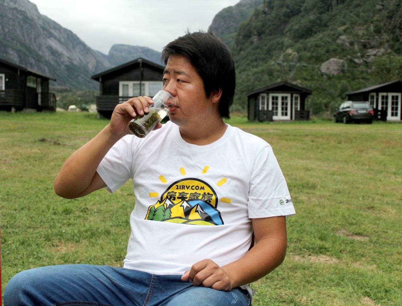 Wang Xudong drikker te han har tatt med seg fra Kina. De har parkert bilen på Lysebotn Camping for tre netter.