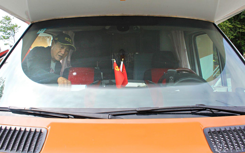 I bilvinduet til Zhu Guoyou og Zhao Yan står flagget til Kinas kommunistparti side om side med landets flagg.