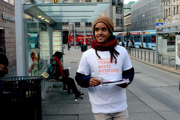 Frivillig Philip Rynning Coker frå Norsk Folkehjelp solidaritetsungdom deler ut avisa «Verdens beste nyheter» ved Jernbanetorget. Foto: Ragnhild Sofie Selstø