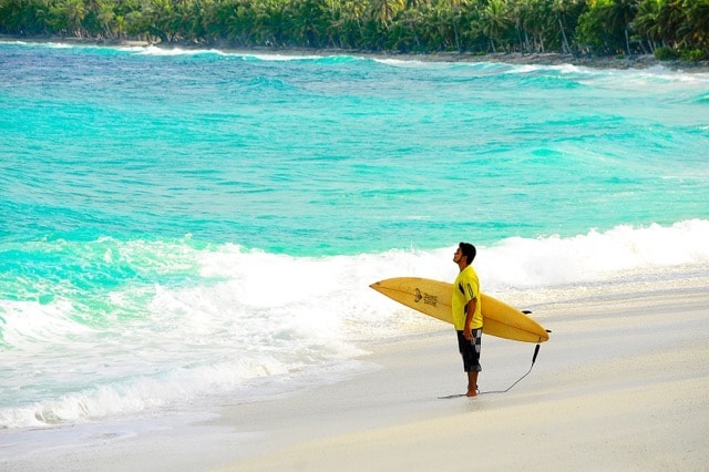 surfer standing at water's edge apprehensive