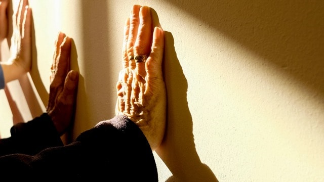 elderly and younger hands pressed against wall