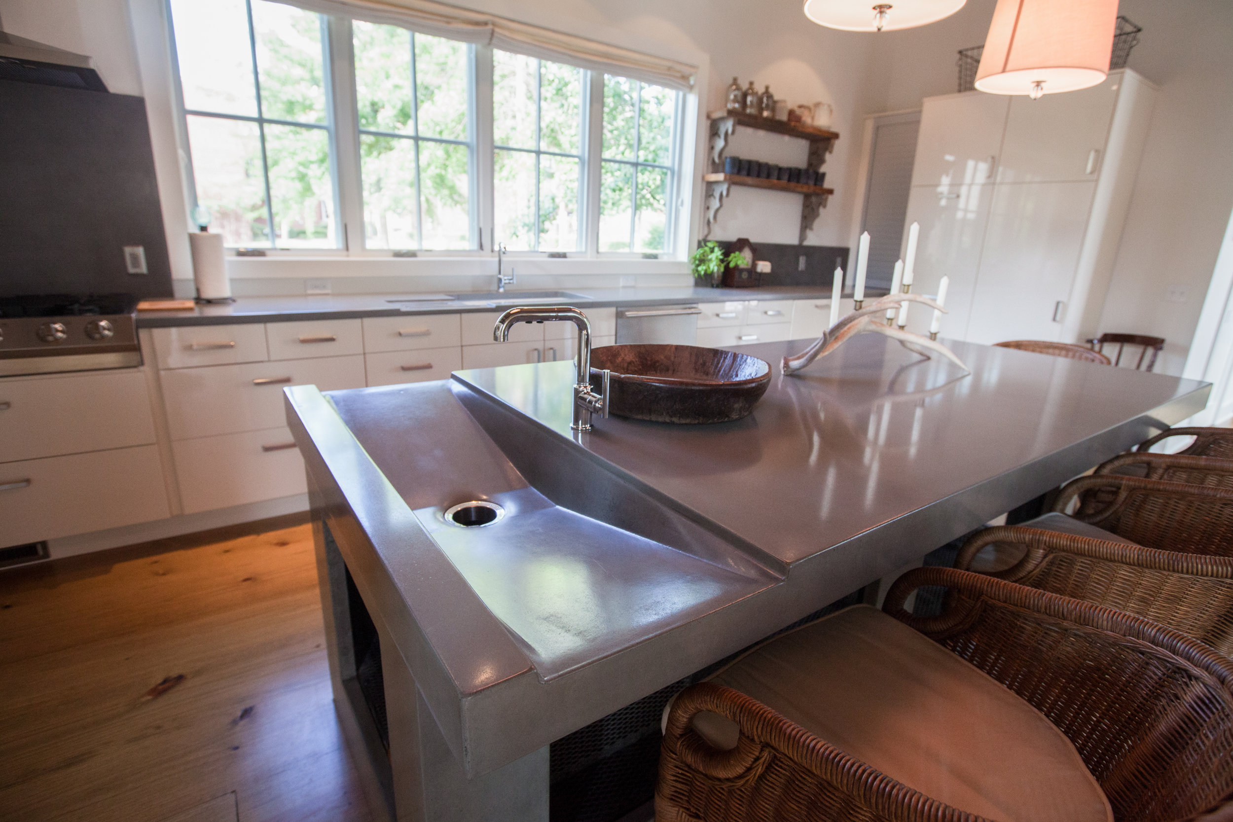 "A solid concrete island with integral sink. The counter and base are all cast from the same concrete. The client was wanting and ""wow"" center piece for their kitchen. This was a beast of an island; it physically and visually anchored the space."