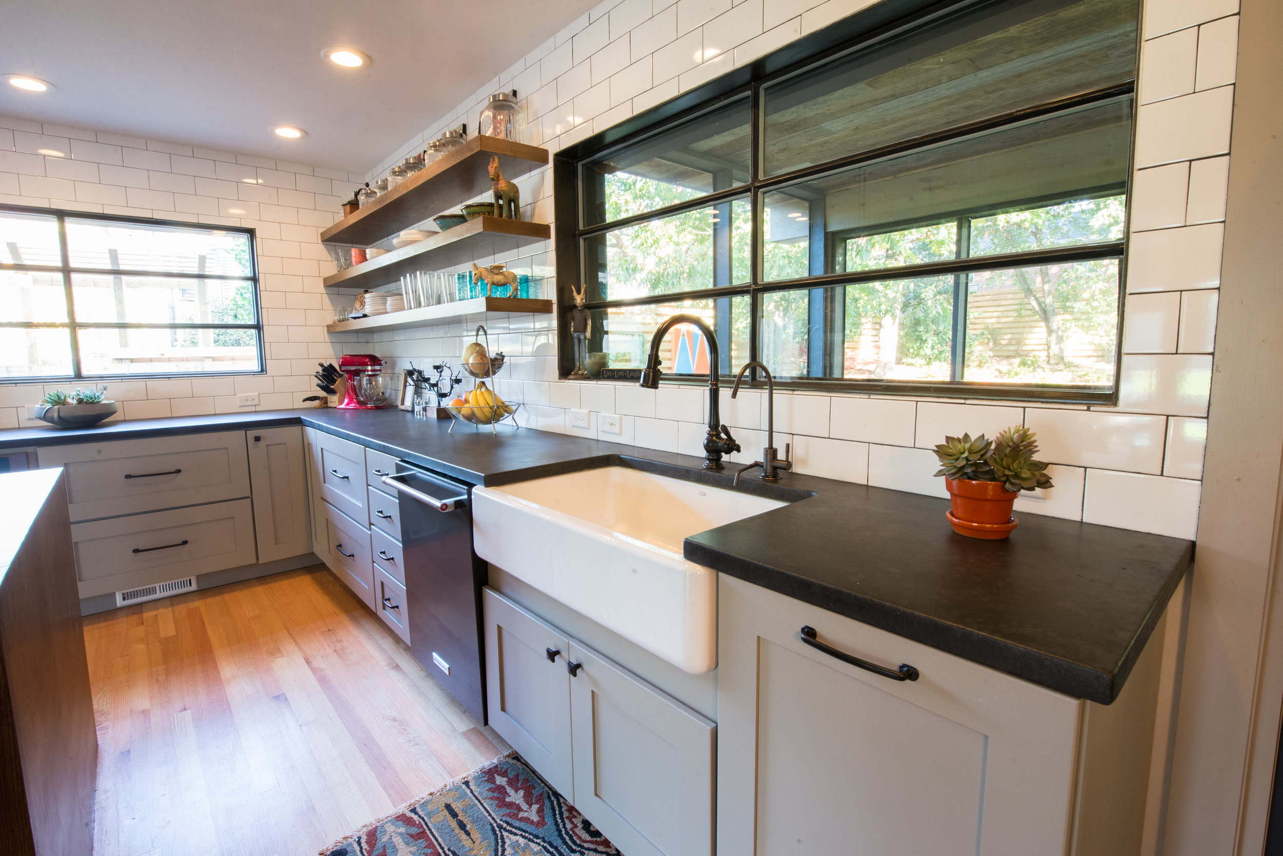 Black concrete offers an elegant counterpoint to the oversized subway tile an farmhouse sink in this kitchen.  #residential