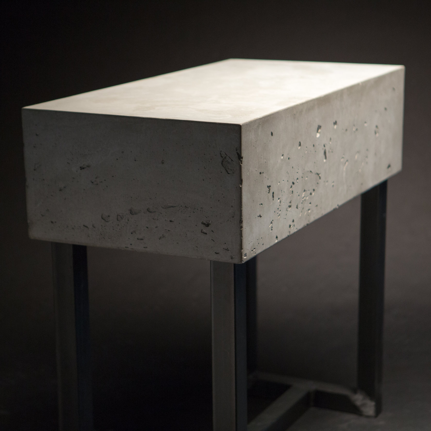 a table with a very thick gray concrete top and a raw welded steel base
