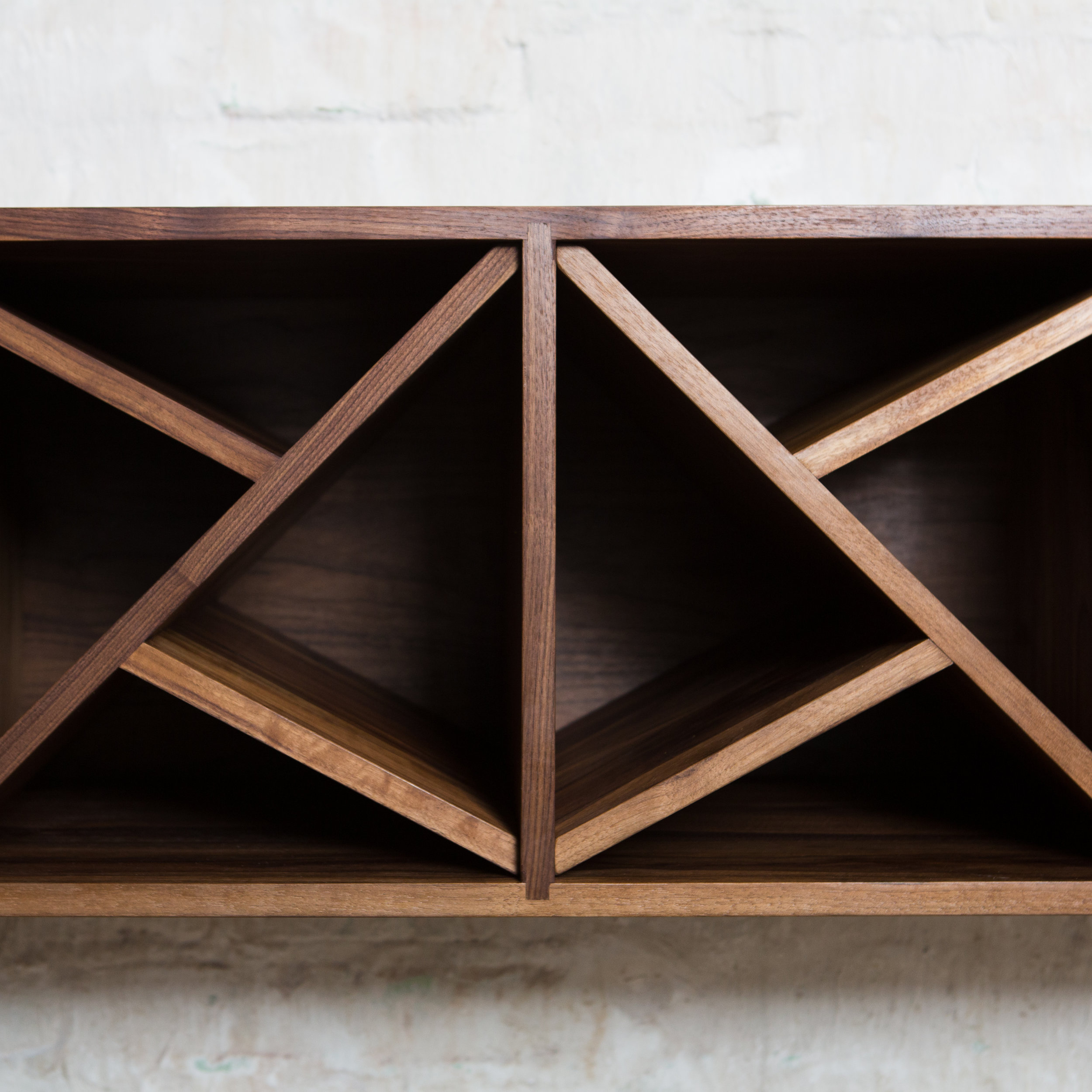 A warm dark stained wood shelving unit with angled shelves.