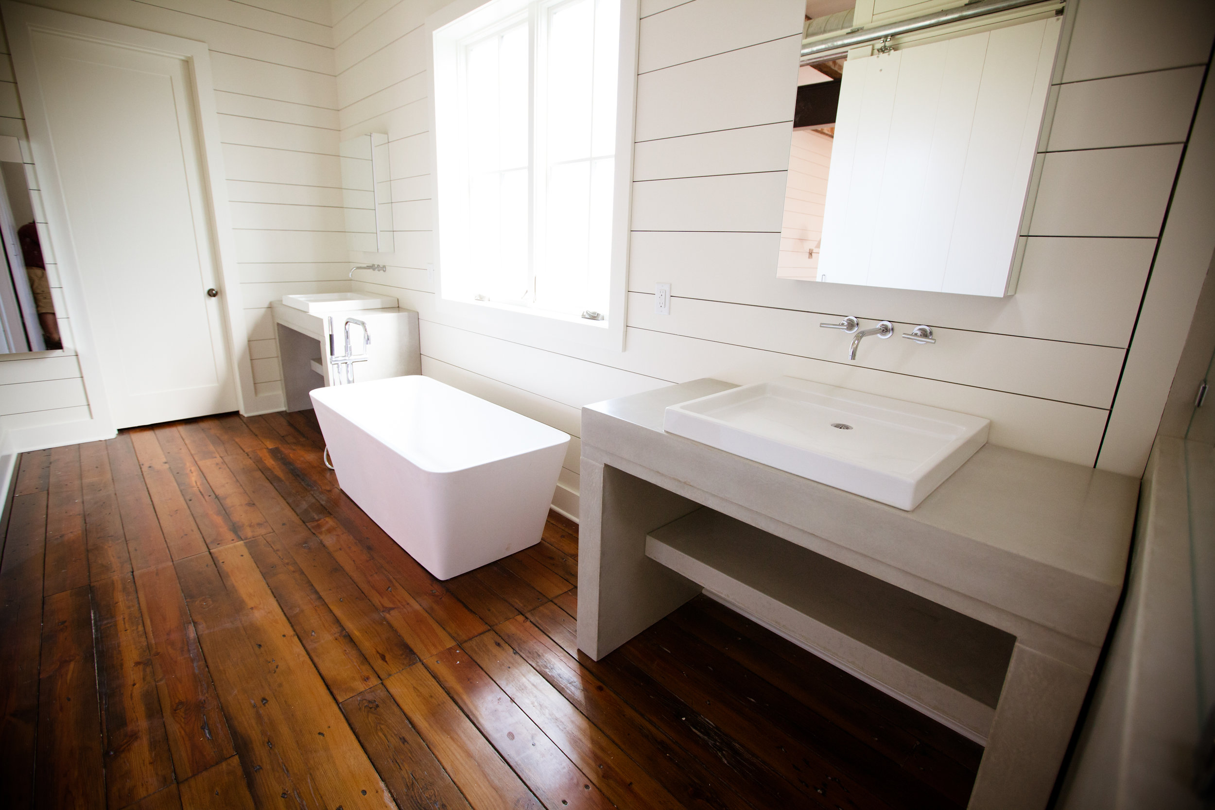 a farmhouse bathroom with concrete vanities and beautiful wood floors