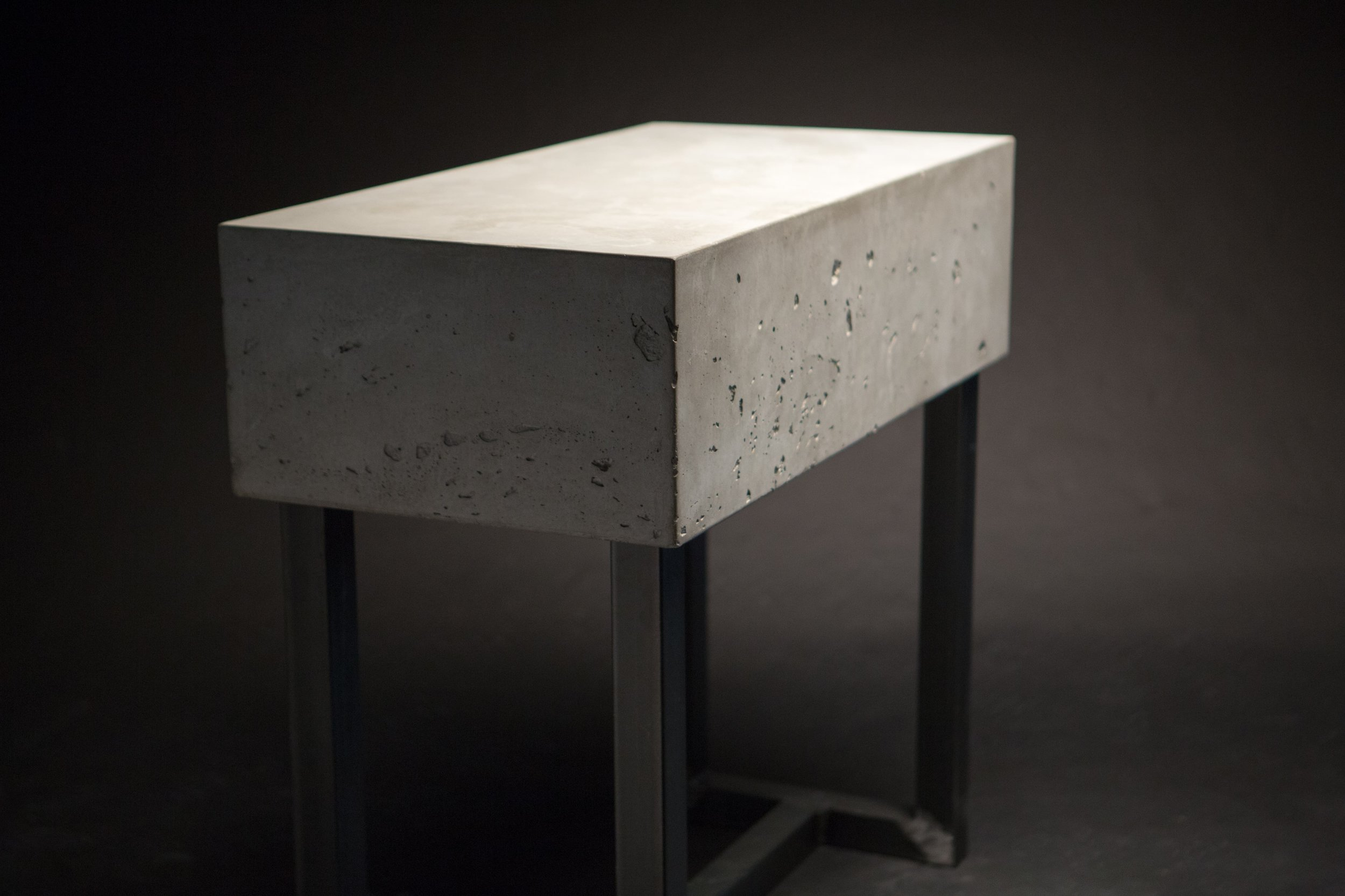 This is a custom concrete and steel side table. The top is a traditional wet cast concrete which gives us the beautiful air voids on the sides and a mottled top.  #furniture