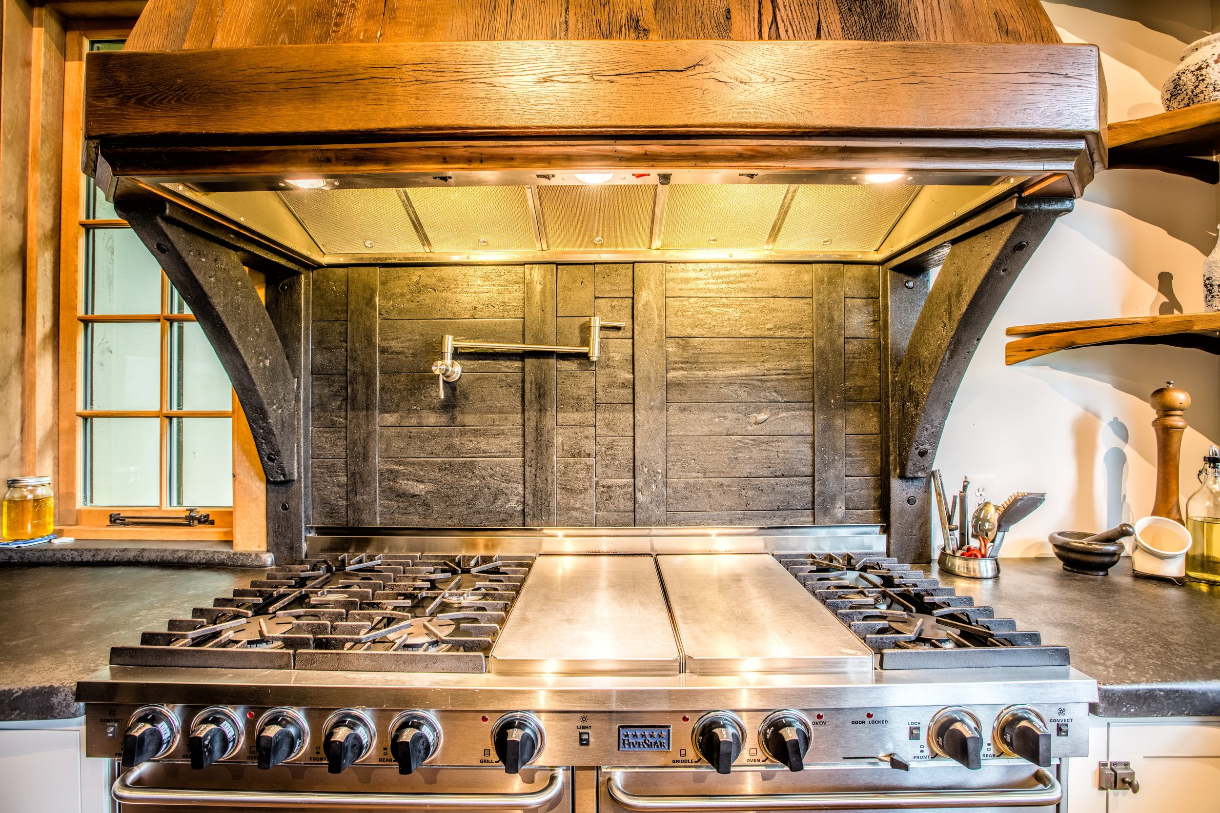A concrete backsplash and hood support cast to look like recovered barn wood. The perfect functional and aesthetic solution because of fire hazard over a gas range. #residential