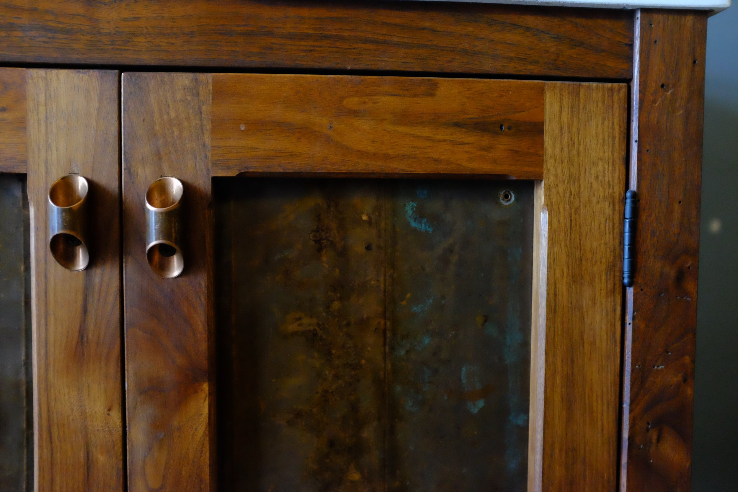 A beautiful custom walnut vanity cabinet using reclaimed copper for the panels and pulls. #residential