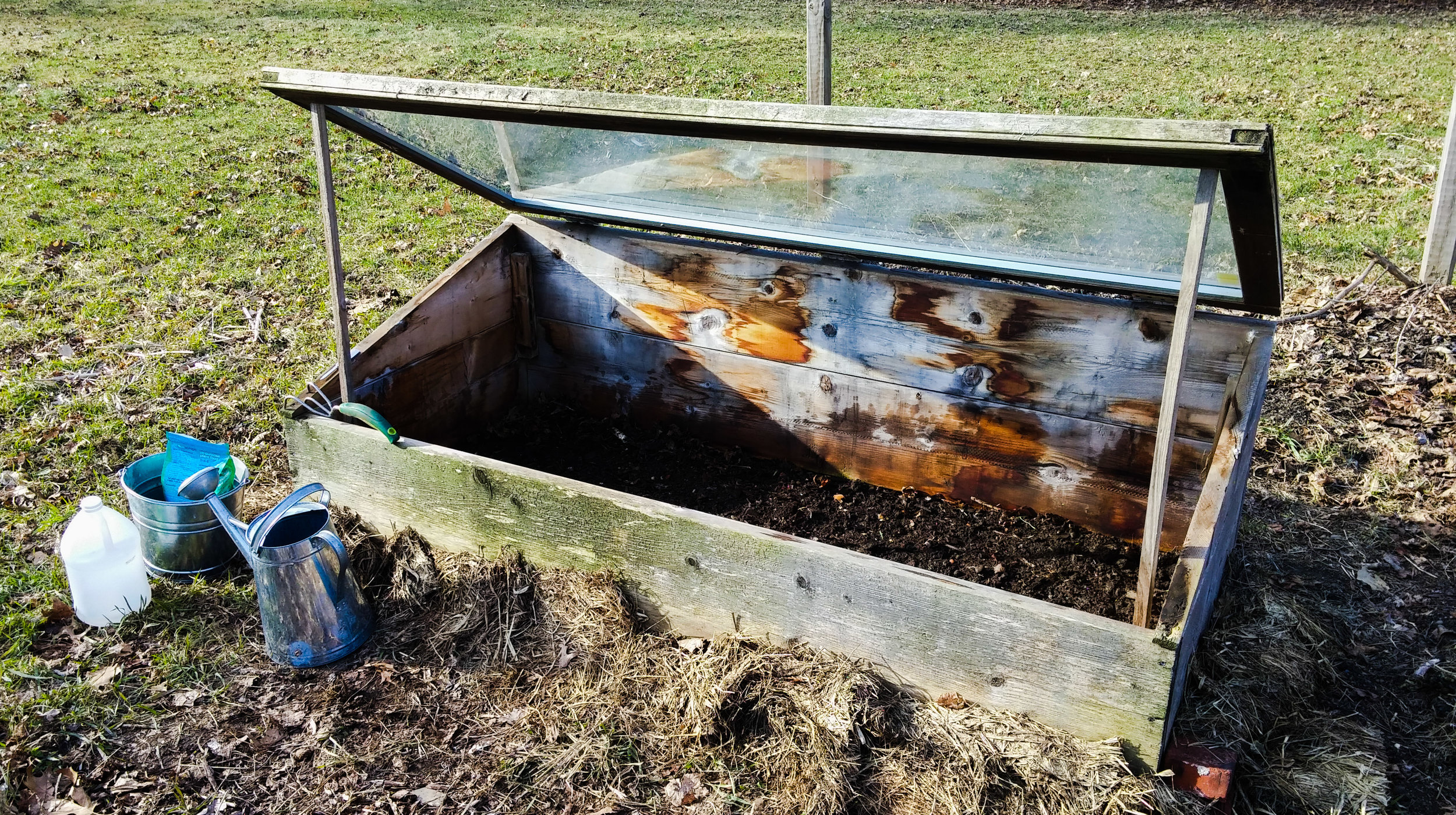 This cold frame will allow us to start salad greens earlier than normal by keeping the seeds and tender plants safe from the still-cold and unpredictable April weather.