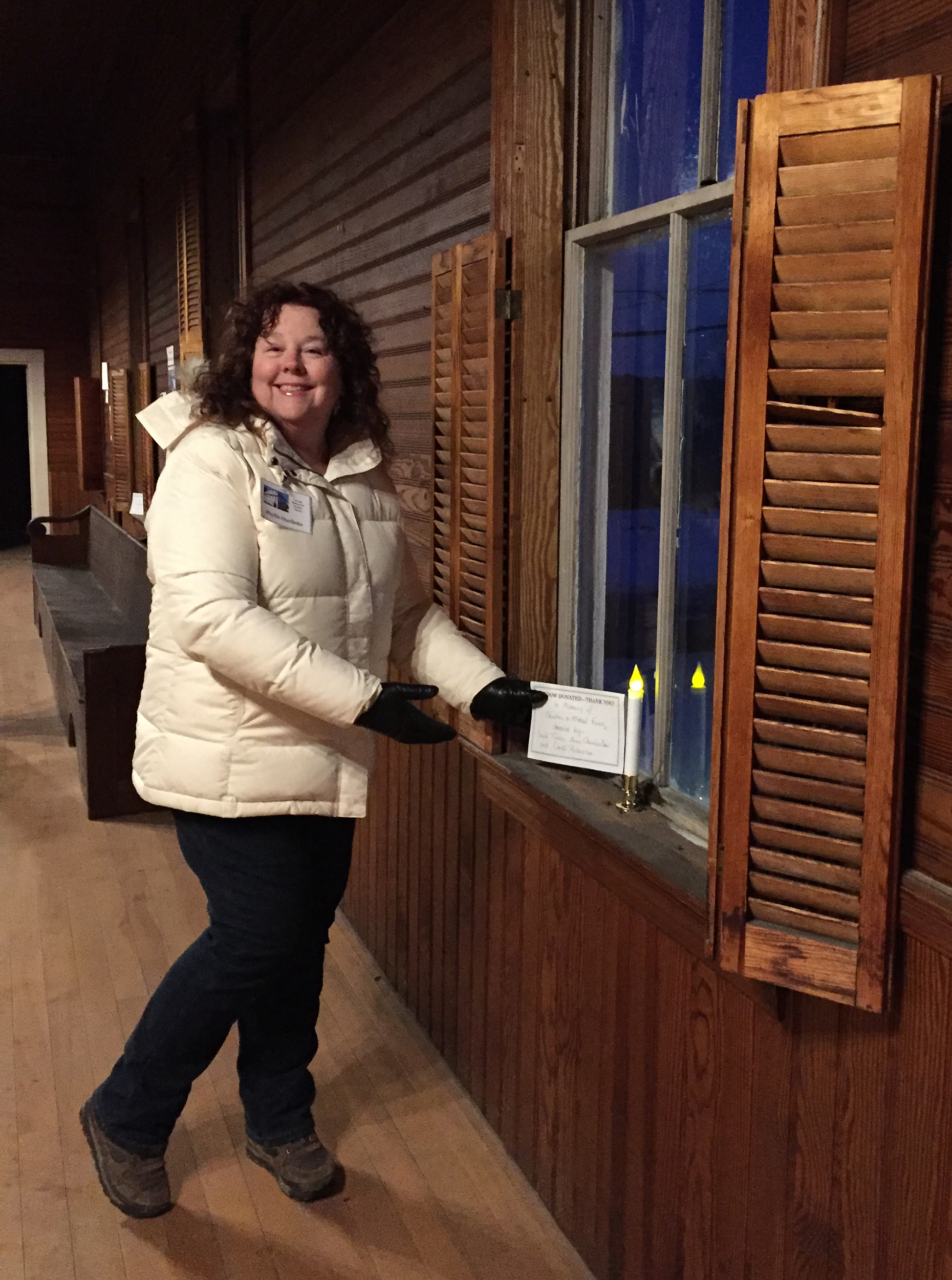 Phyllis Ouellette places one of the window donation signs during the Open House night.