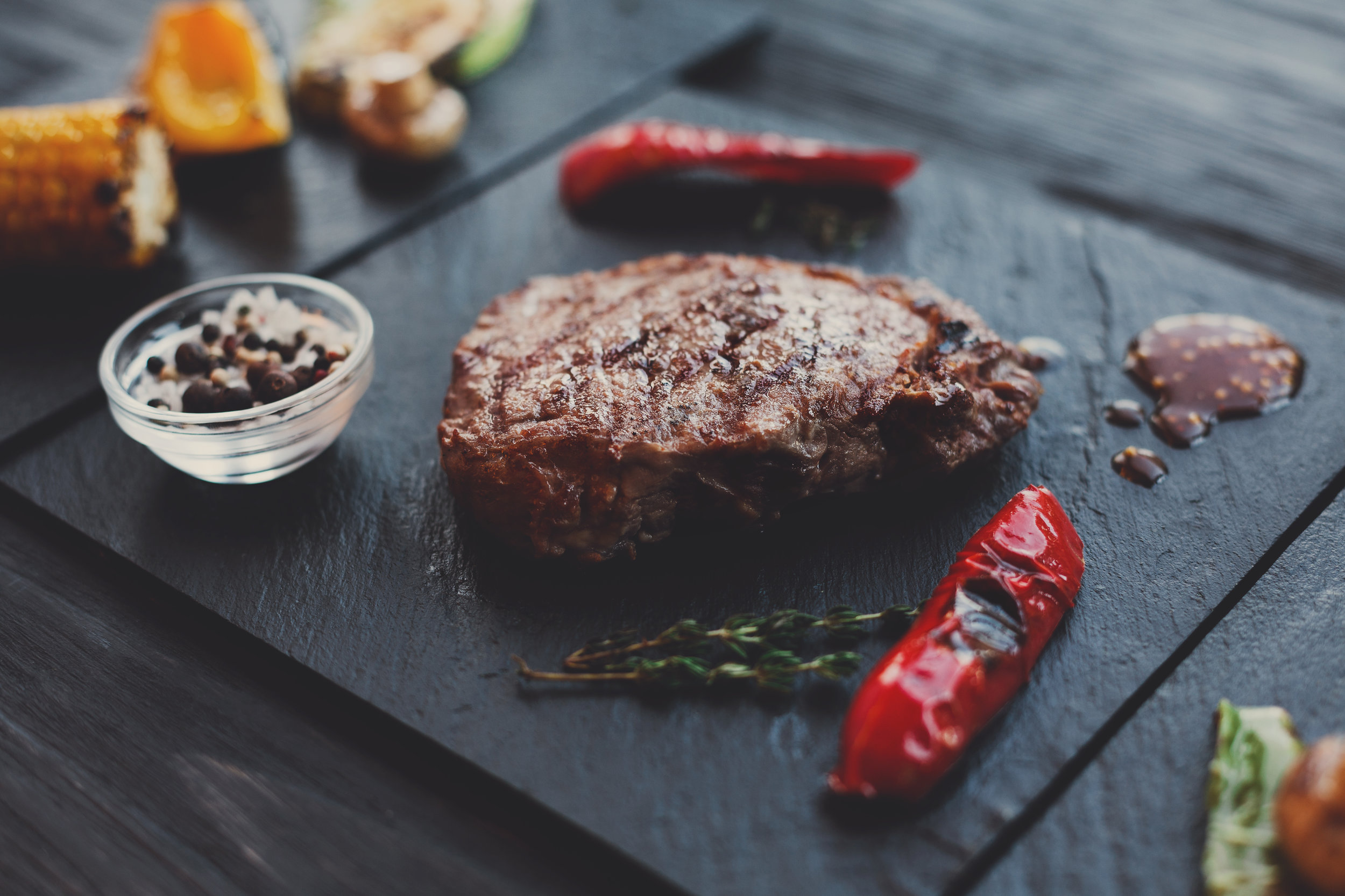 grilled-beef-steak-closeup-on-dark-wooden-table-PVGVZXS.jpg