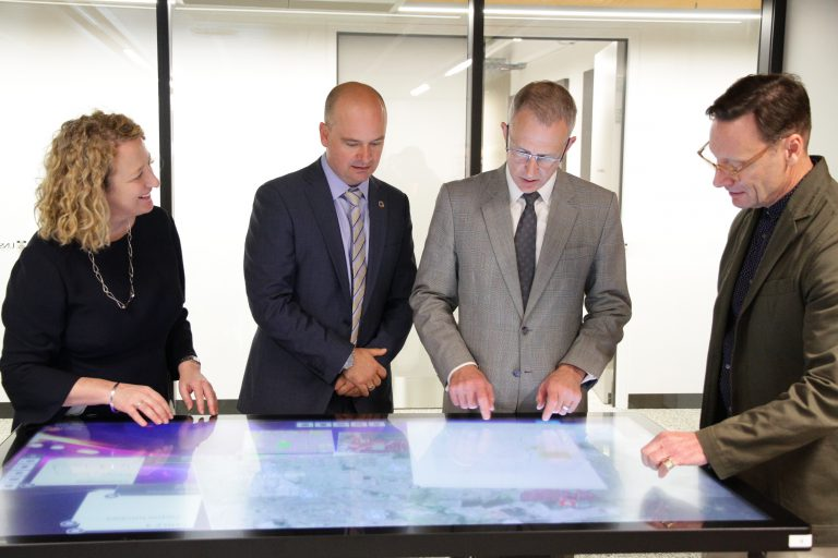 UNSW VP of External Relations, Fiona Docherty, Professor Chris Pettit, chair of Urban Science, minister Fletcher and Professor Bruce Watson, Head of School/Deputy Dean Built Environment interact with the RAISE tool in the UNSW City Analytics Lab.Image provided by UNSW External Relations.