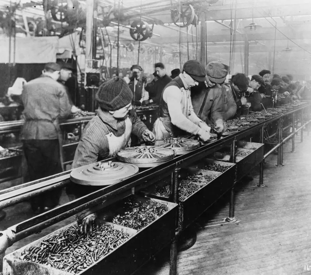 Workers on the first moving assembly line put together magnetos and flywheels for 1913 Ford automobiles.