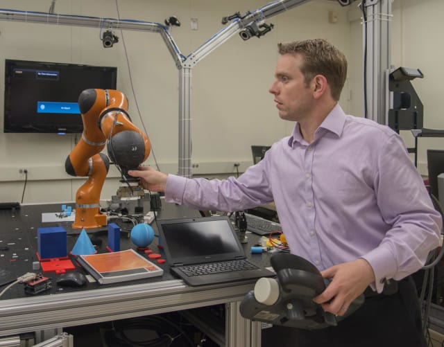 NIST engineer Jeremy Marvel adjusts a robotic arm used to study human-robot interactions. (Image courtesy of Fran Webber/NIST/)