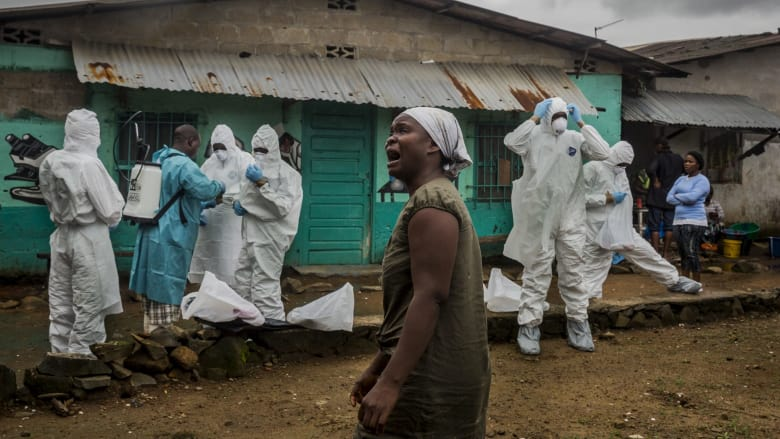 A relative grieves as a Red Cross burial team prepares to remove the body of an Ebola victim in central Monrovia, Liberia. Photo:Daniel Berehulak/New York Times