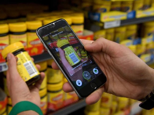 Woolworths employee Bryn Rayfield uses the new Scan & Go app at the Double Bay store in Sydney. Picture: Dan Himbrechts  Source:AAP