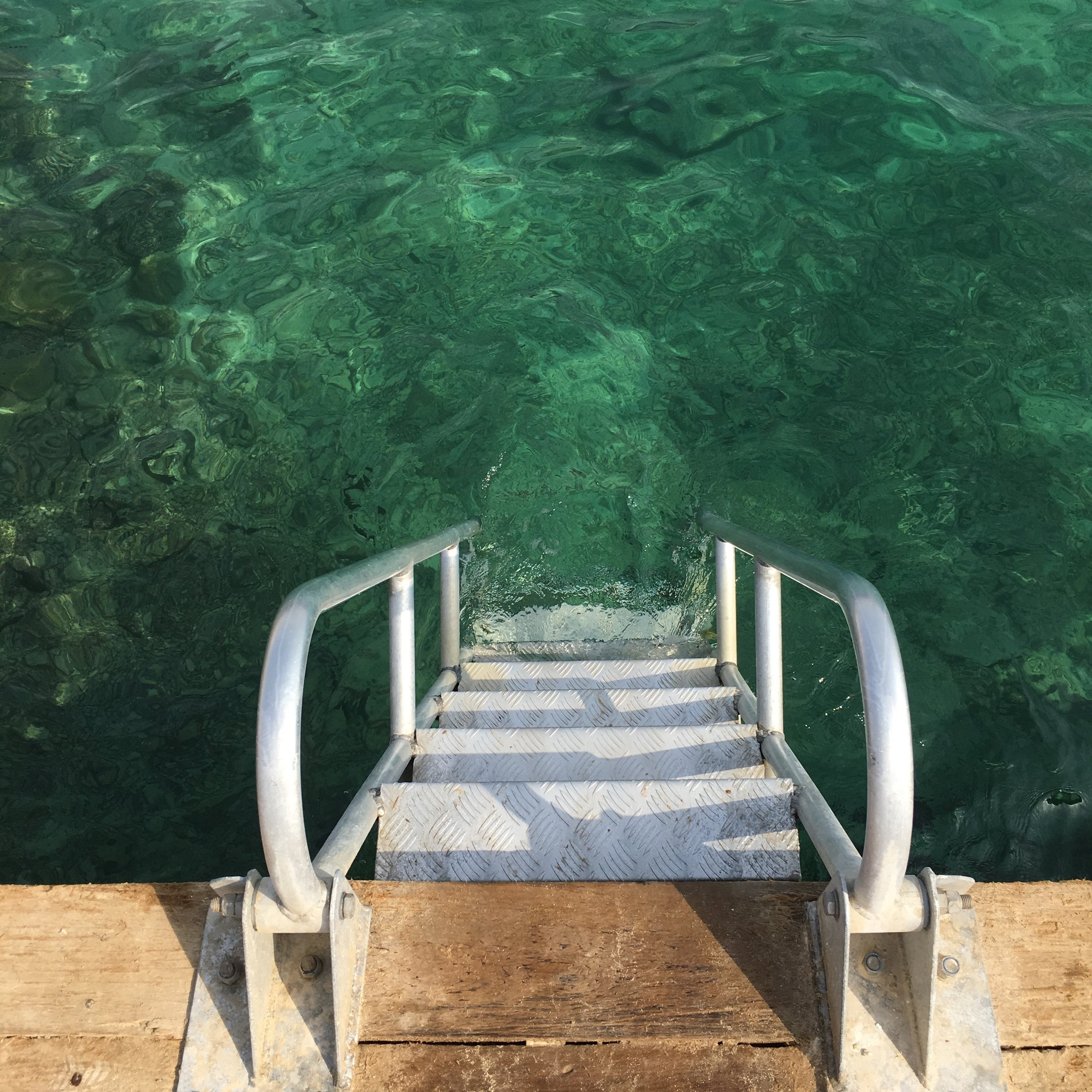 The stair from the wooden deck down to the beautiful water