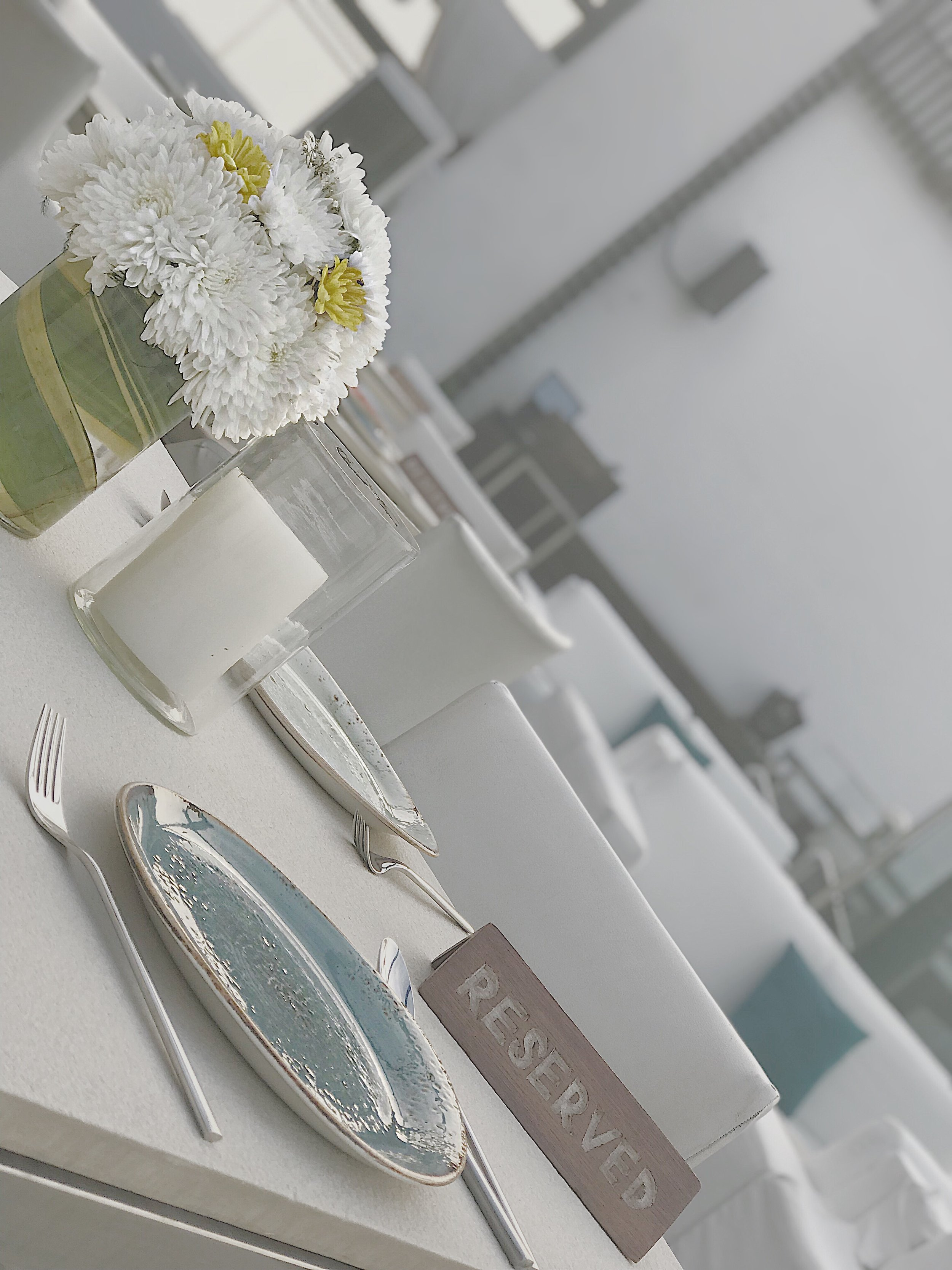 Pretty setting with flowers, candles and white interior at the Asilo roof top