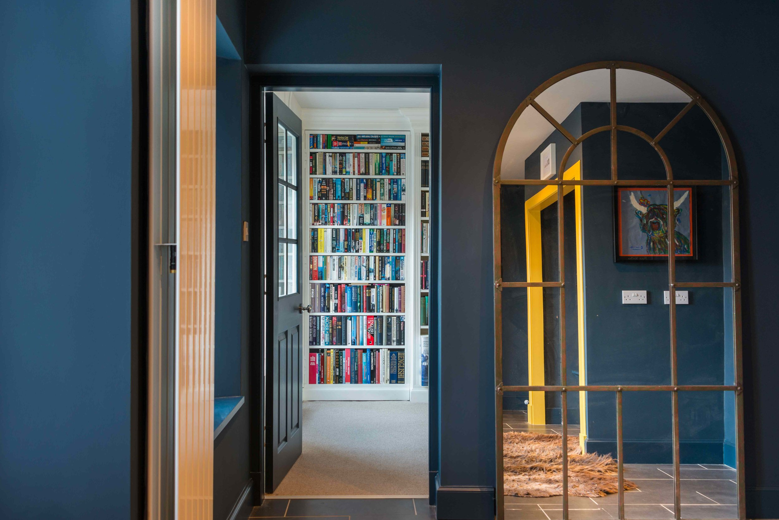 Floor to ceiling painted bookcase scheme with secret door.