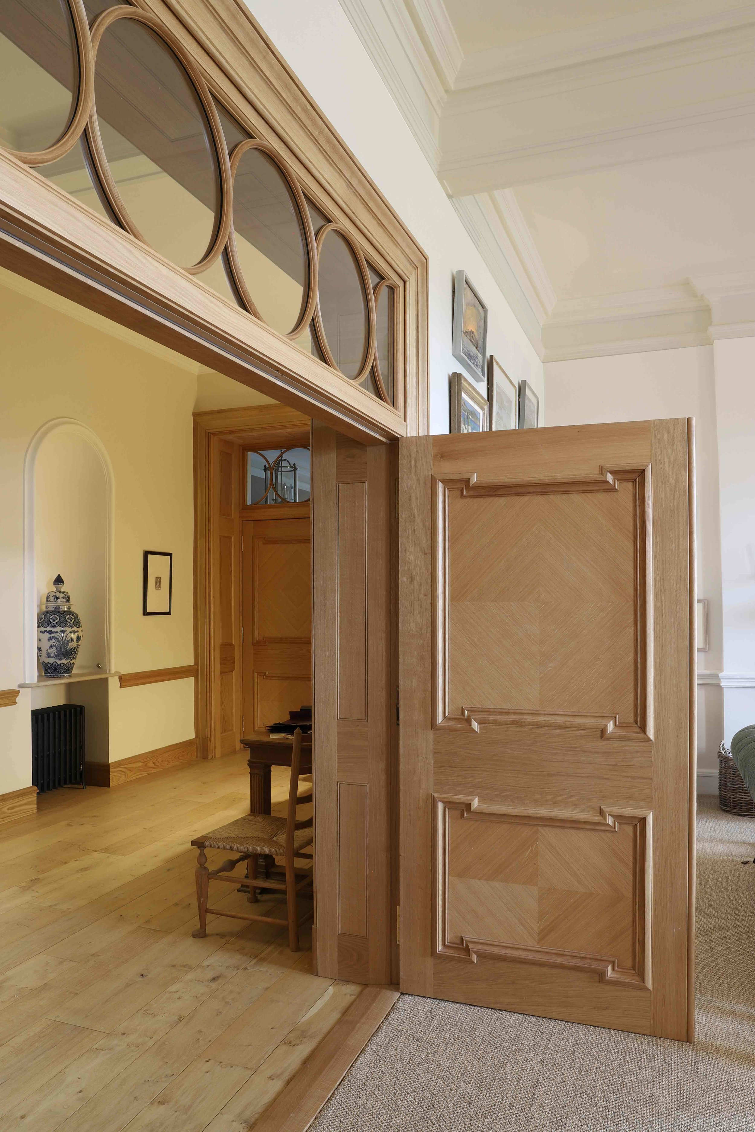 Oiled oak door screen, circular astragals and quarter matched panels, Marchmont house, Greenlaw.