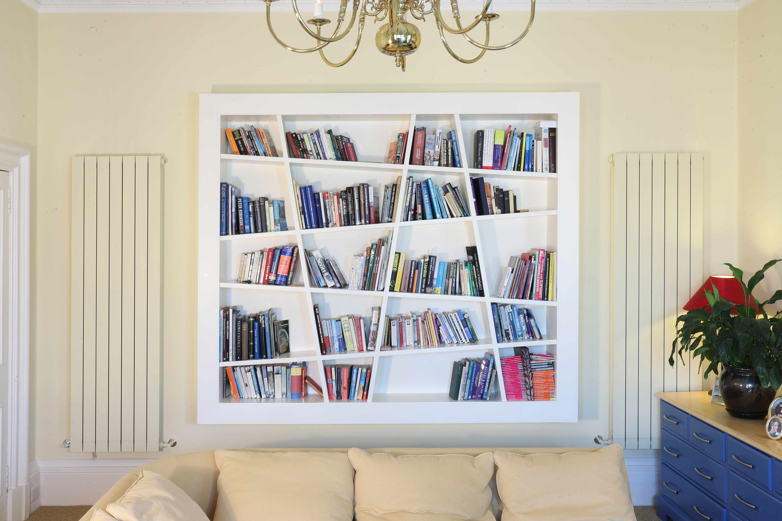 70's style wall mounted bookcase with LED surround lighting for a period house in the Grange.