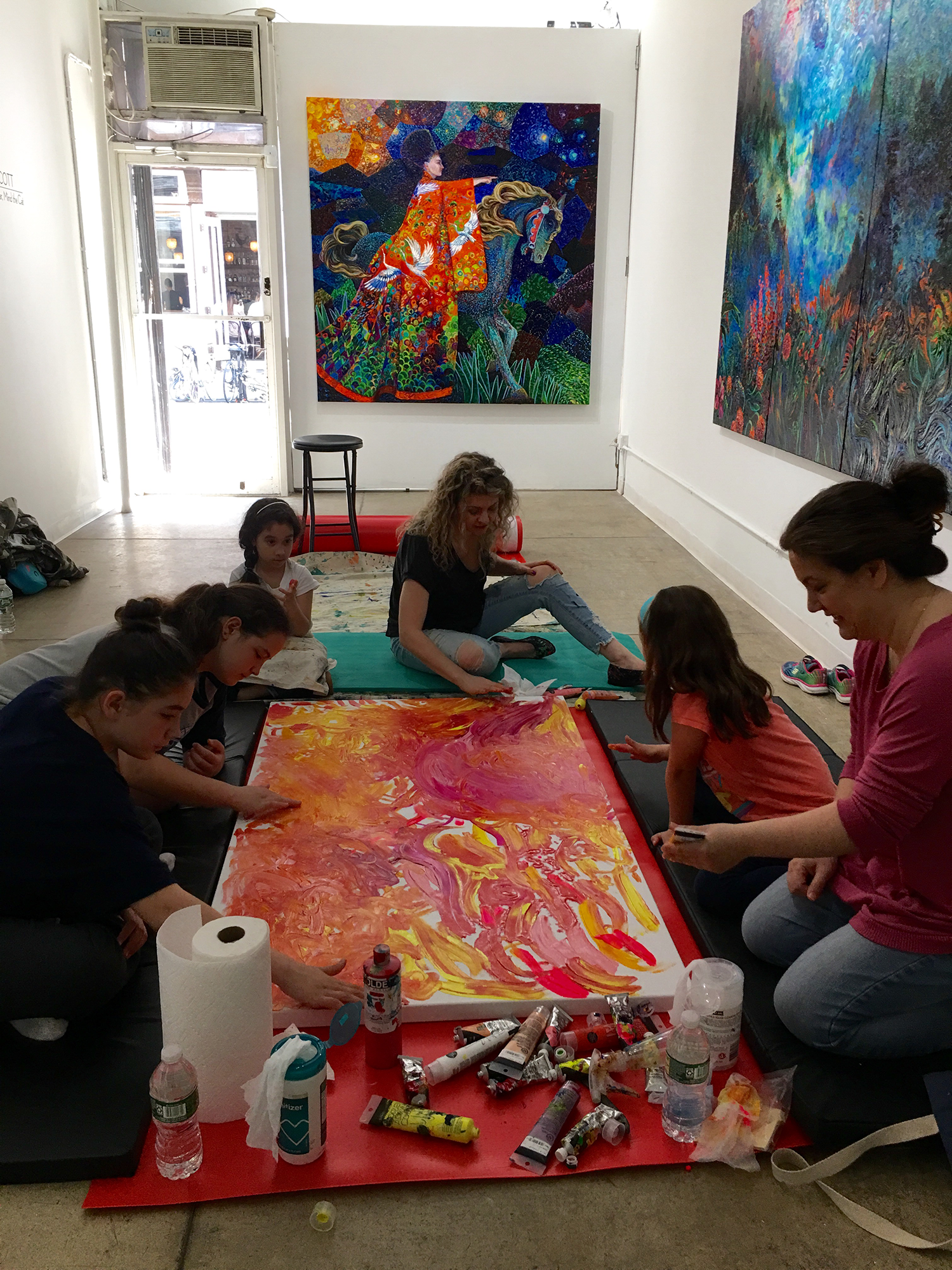 Children creating finger paint art with Artist Iris Scott.png
