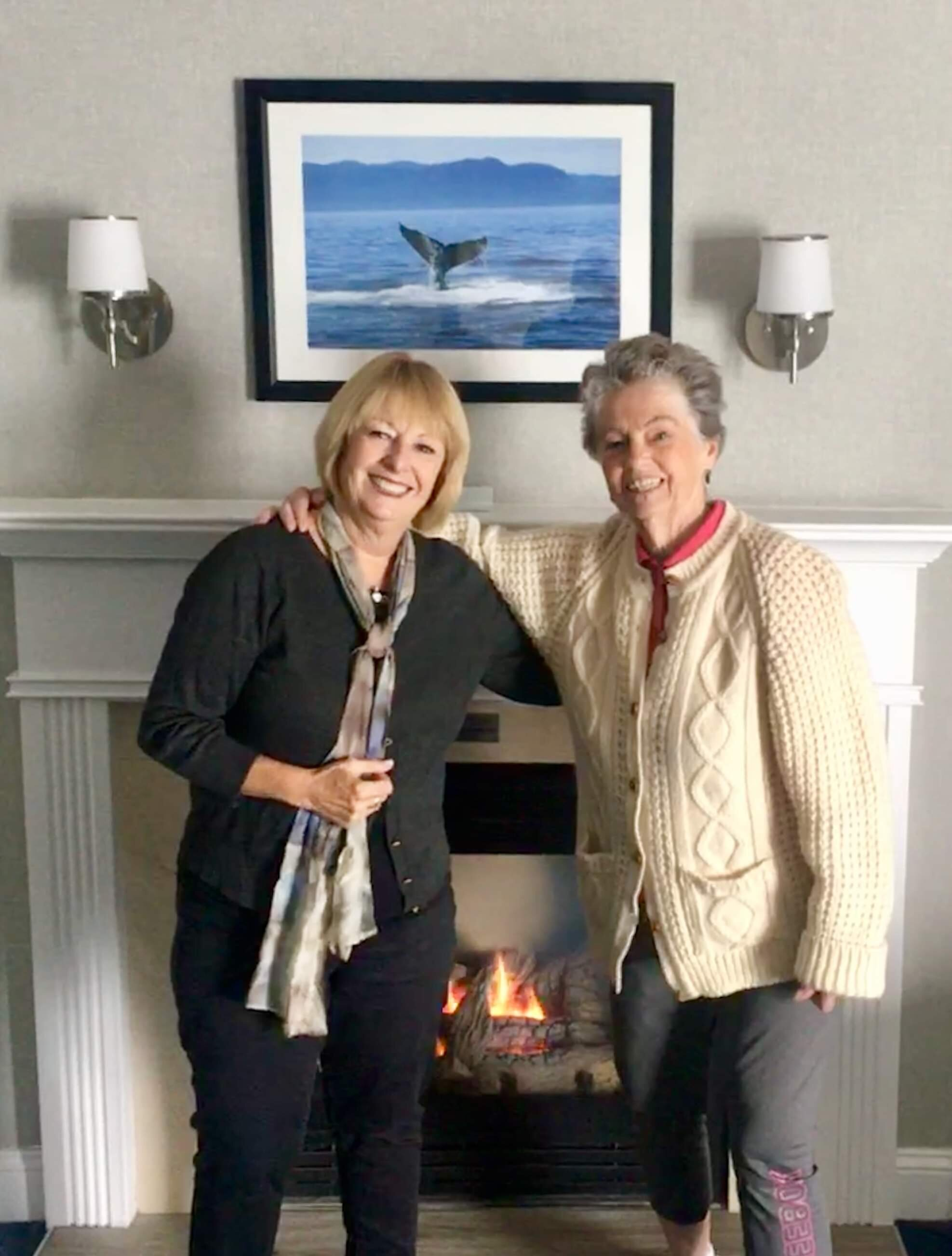 Carol with sister Joan and our inviting fireplace