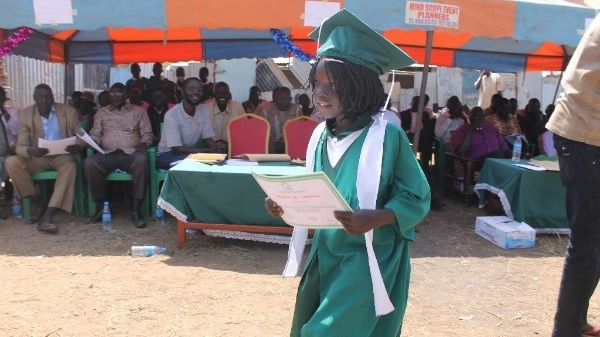 A student at Good Shepherd Academy in Juba, South Sudan, proudly carries her academic awards at the end of the term.