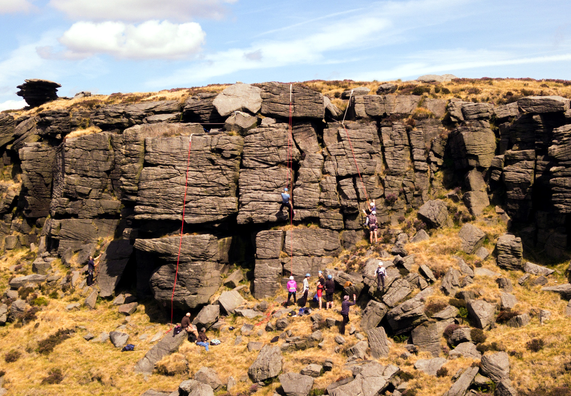 Group enjoying a sunny day rock climbing in the Peak District
