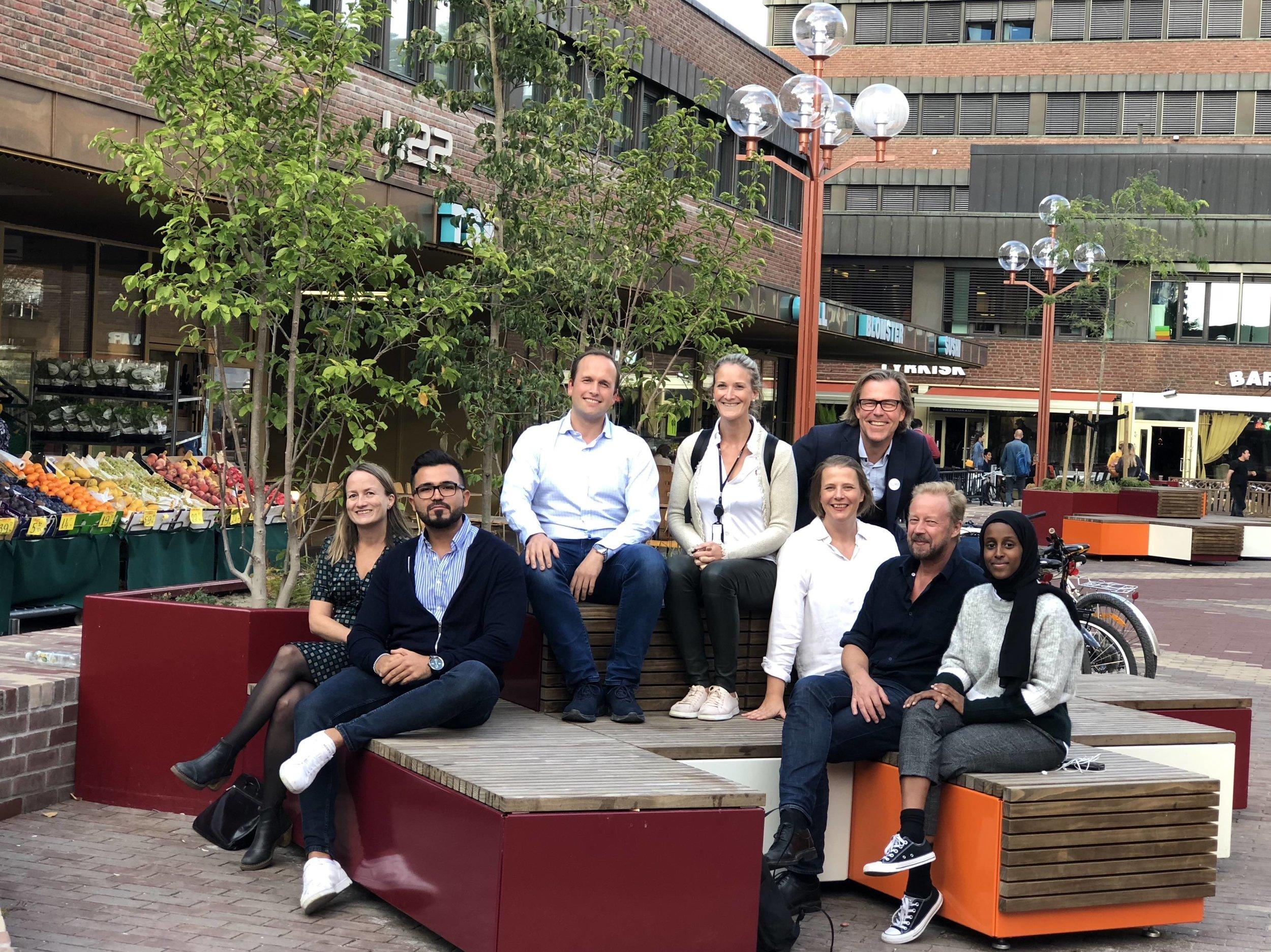 Det stiftende styret samlet på torget. Fra venstre: Kjersti Grut (Områdeløftet), Omid Kamizi (Tøyen Blomster), Morten Rye Pedersen (Hagegata 27 og konstituert styreleder), Tine Rustberggard Bjørn (Entra), Vigdis Tvedt (Bydel Gamle Oslo), Øystein Aurlien (ansvarlig for prosjektet), Reinert Mithassel (Deichman) og Ruwayda Mohamud (beboerrepresentant). En av de andre beboerrepresentantøne, Janic Heen, fikk ikke vært tilstede under fotograferingen. Foto: Shenel Shonol