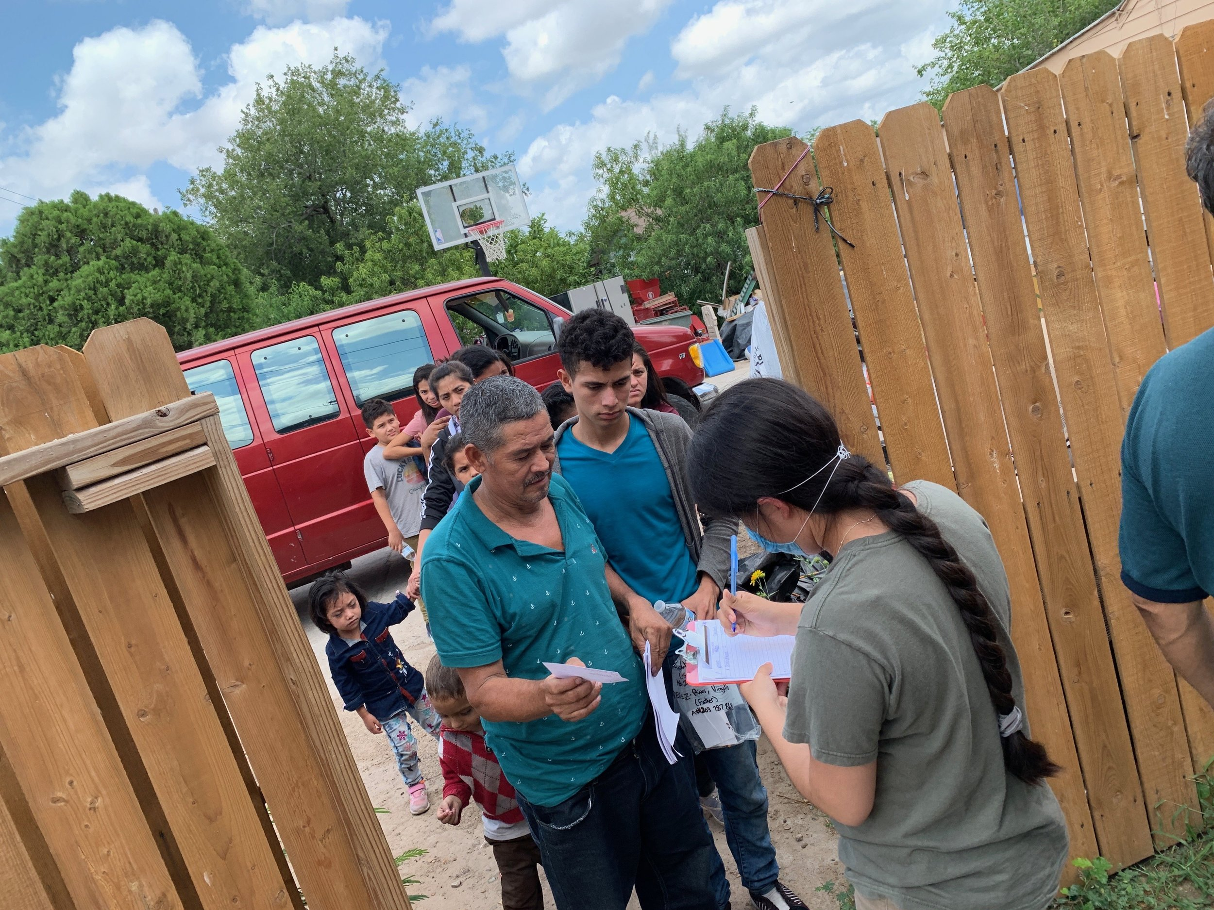 Refugees forming a line to show their documents given by ICE in order to call their relatives for a bus or plane ticket.