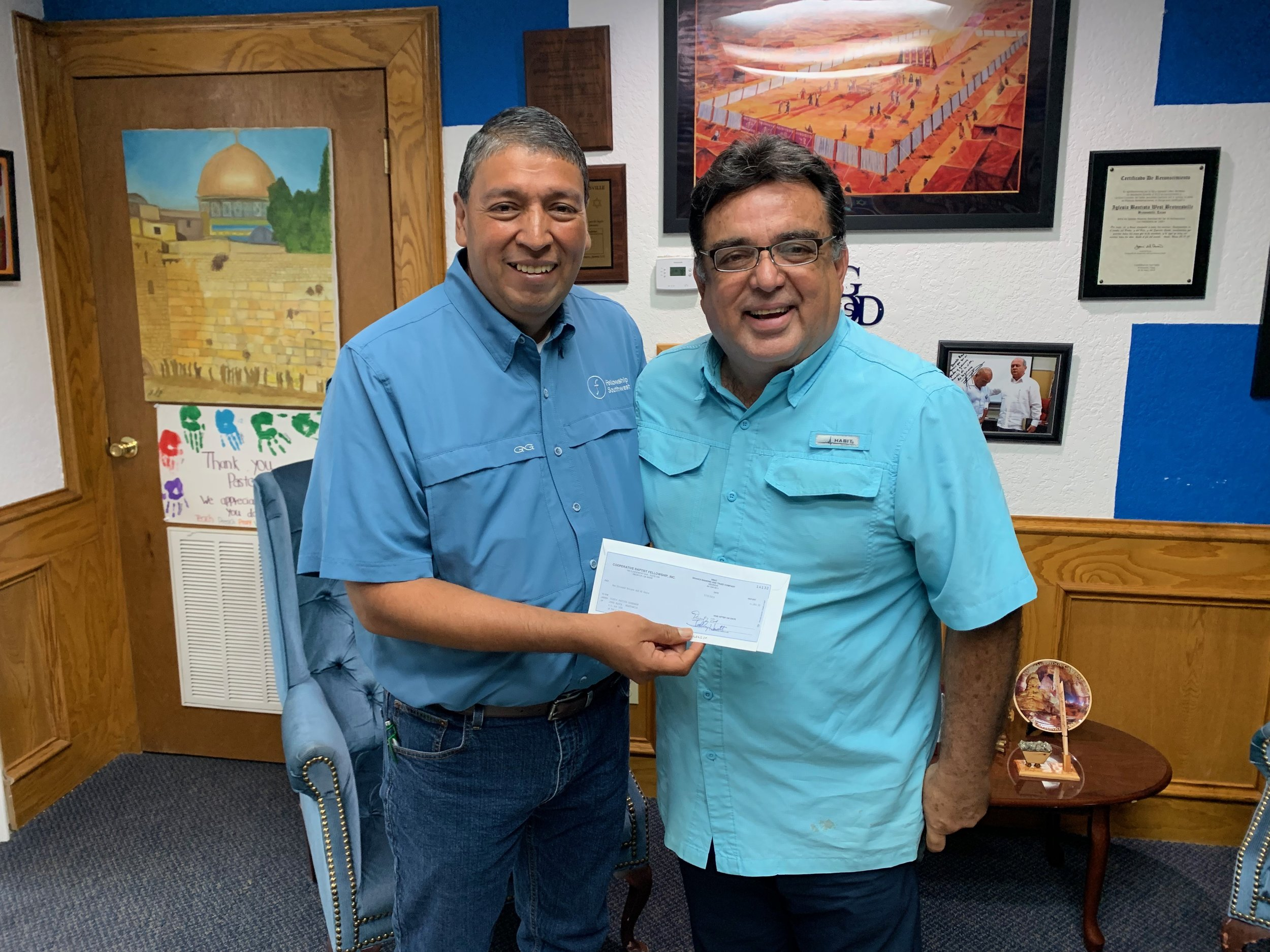 Jorge Zapata (left) of CBF Texas/Fellowship Southwest, presents a check for $1,000 to Rogelio Perez, pastor of Iglesia Bautista Capernaum in Brownsville, Texas. Twice a week, the congregation feeds asylum seekers on the border bridge between Brownsville and Matamoros, Mexico.