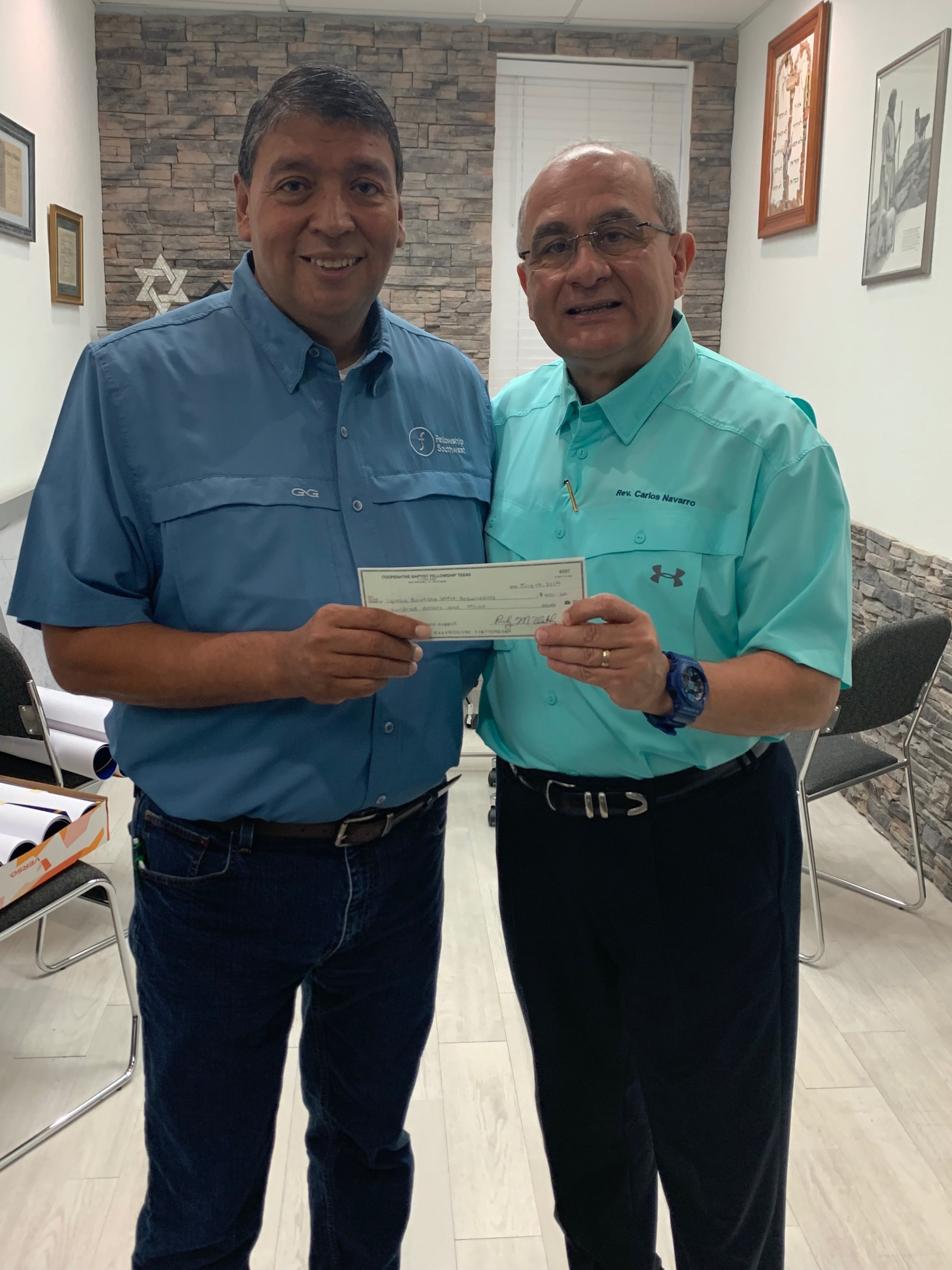 Carlos Navarro, (right) pastor of Iglesia Bautista West Brownsville in Brownsville, Texas, receives $5,000 for the church's ministry to asylum seekers from Jorge Zapata of CBF Texas/Fellowship Southwest. The congregation shelters 60 to 70 refugees per day in its facilities.