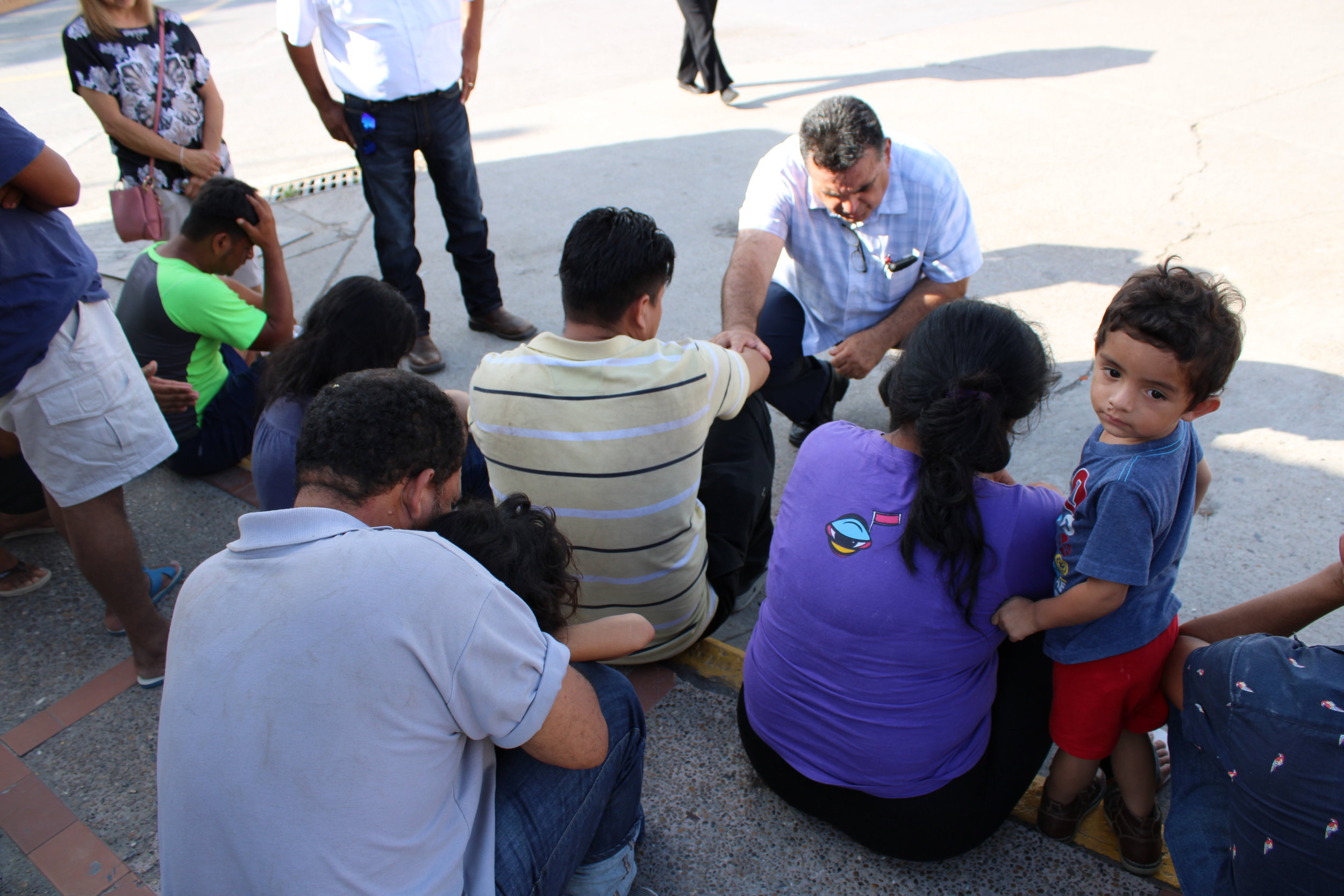 Rogelio Perez, leading prayer in top center