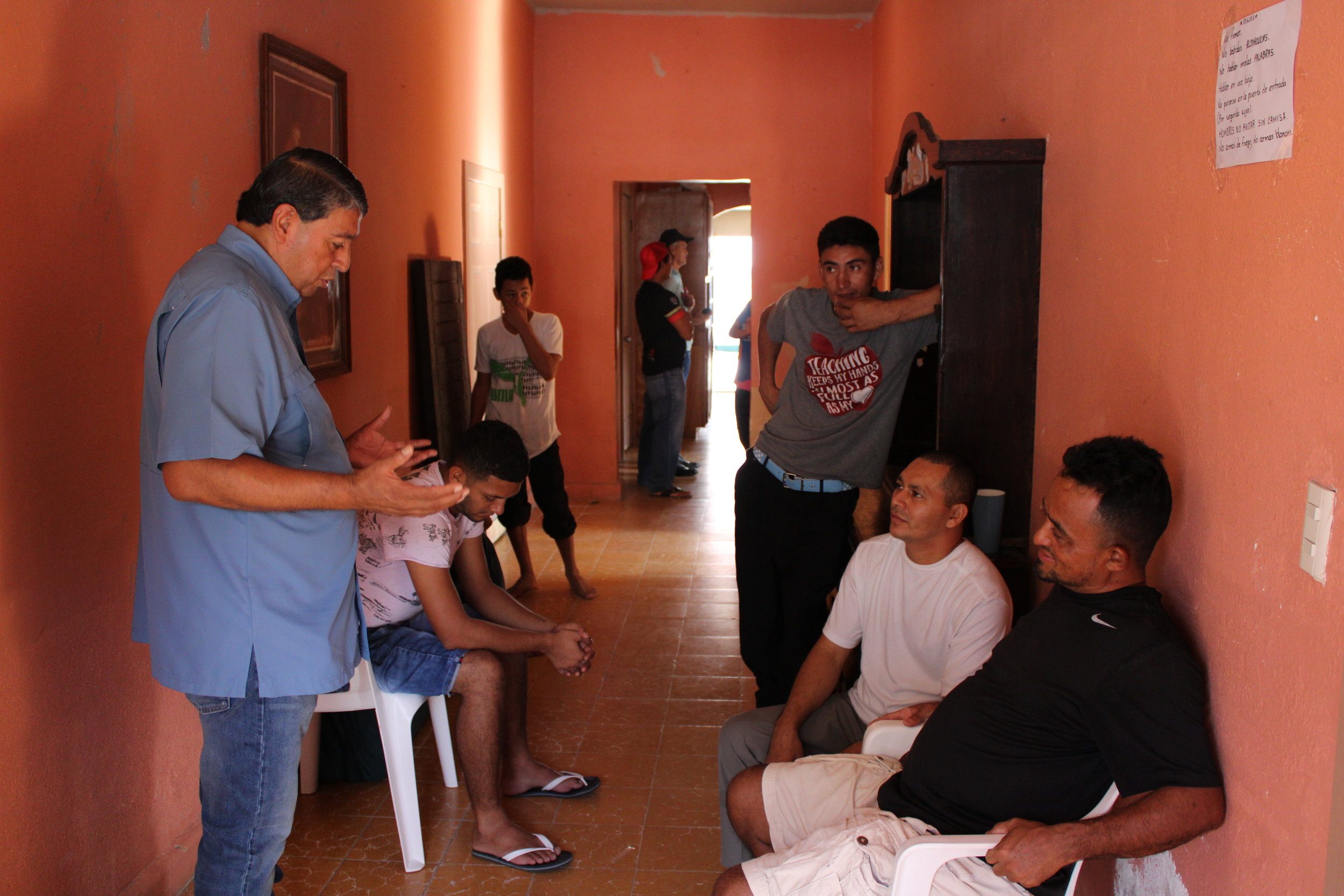 Jorge Zapata, praying with refugees in a shelter operated by Lorenzo Ortiz